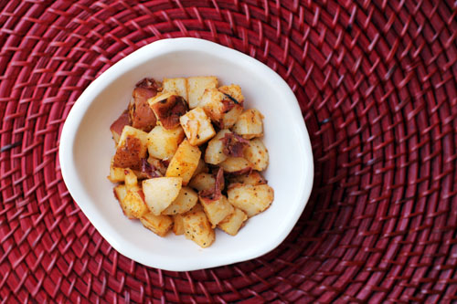 skillet fried potatoes cut into chunks in a white bowl