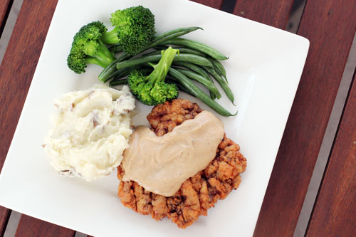 top view of chicken fried steak on a plate with mashed potatoes and vegetables