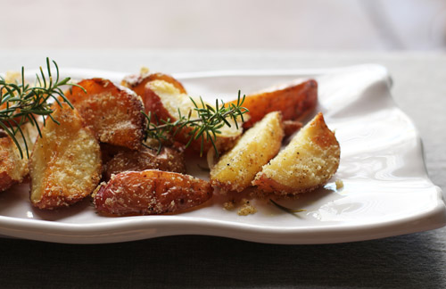 front view of roasted potatoes and rosemary sprigs on a plate that is white