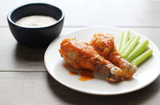 Backlit side view of gluten-free buffalo chicken drumsticks with celery sticks and blue cheese dressing