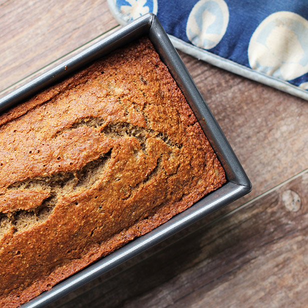 Top view of gluten-free banana bread in a pan with a blue potholder