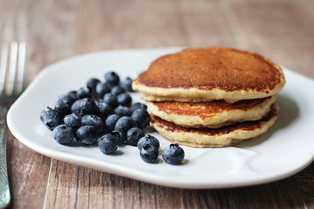 Side view of gluten-free, dairy-free banana oat pancakes with blueberries on the side
