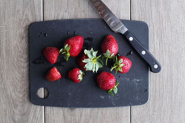 Whole washed strawberries on a black cutting board