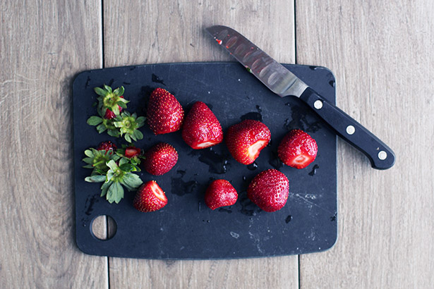 Strawberries on a cutting board with tops cut off
