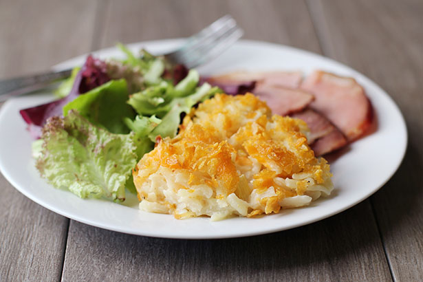 Funeral Potatoes on a plate with salad and ham