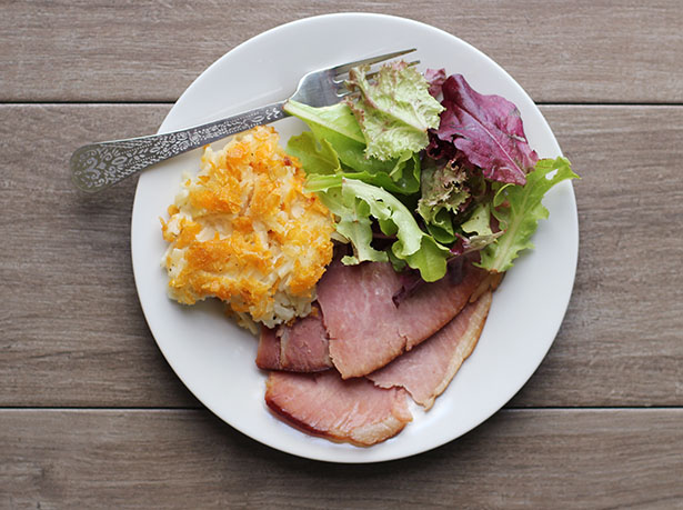 Top view of a plate of food with potato casserole, ham and salad