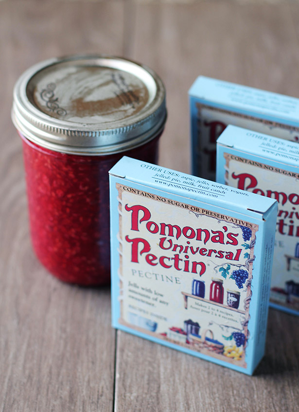 Boxes of Pomona's Universal Pectin in front of a jar of raspberry freezer jam