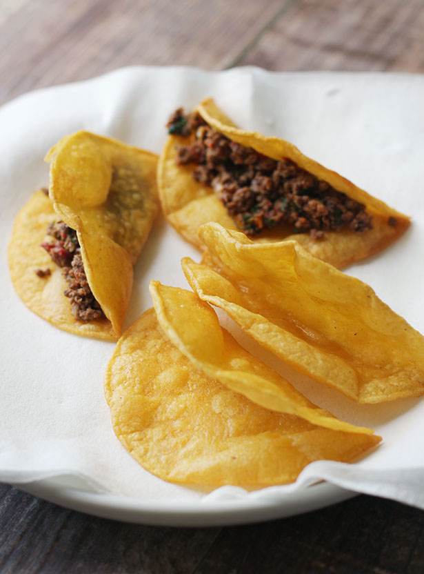 Homemade crispy tacos shells on a plate, two empty two with meat